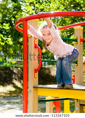 Cute girl on outdoor playground equipment - stock photo