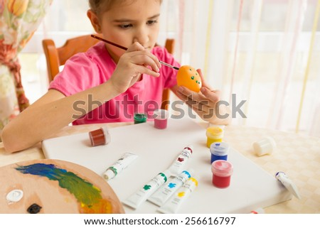 Cute girl painting colorful eggs for Easter - stock photo