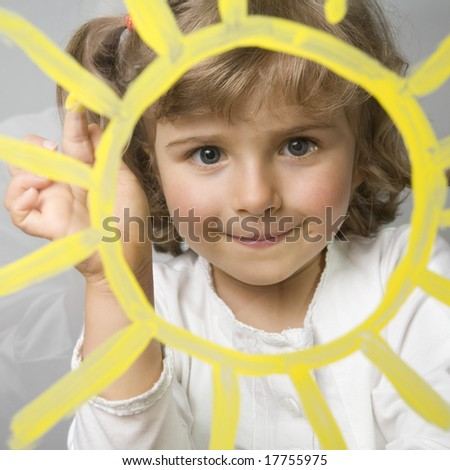 Cute girl painting  sun on glass - stock photo