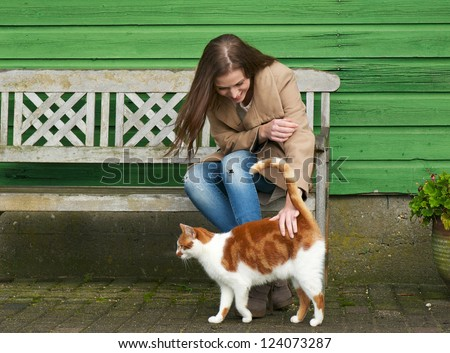 Cute girl petting a furry cat outdoor. Sitting on wooden bench with green wall background - stock photo