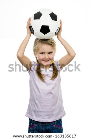Cute girl playing football, happy child, young female goalkeeper enjoying sport game, holding ball, isolated portrait of a preteen smiling and having fun, kids activities, little footballer  - stock photo