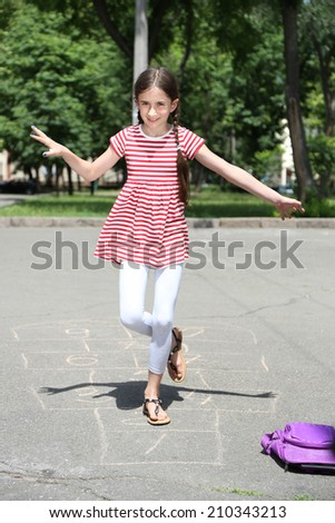Cute girl playing hopscotch outside - stock photo