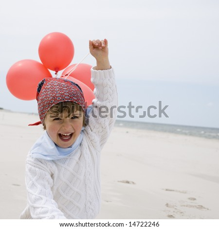 Cute girl playing with balloons on the beach - stock photo