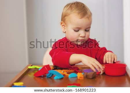 Cute girl playing with dough - stock photo