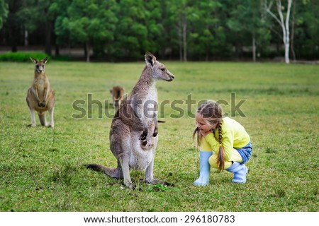 cute girl playing with kangaroo at zoo - stock photo