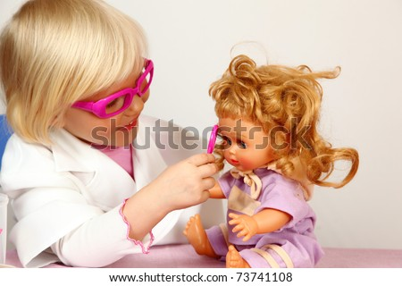 cute girl plays in doctor with doll - stock photo
