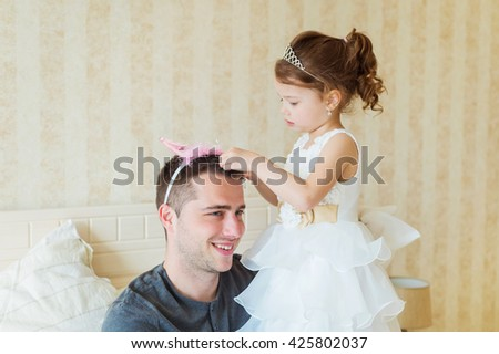 Cute girl putting a crown on her father head. Young father is enjoying time with his child. Father and daughter at home. Handsome father with little girl. Happy father and daughter. - stock photo
