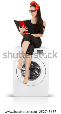 Cute Girl Reading a Book on a Washing machine - Young housewife doing laundry and reading   - stock photo