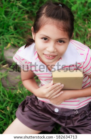 cute girl reading book in garden - stock photo