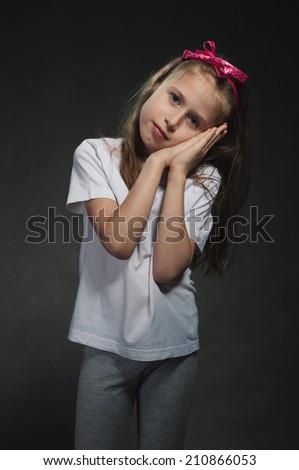 Cute girl showing sleep gesture - stock photo