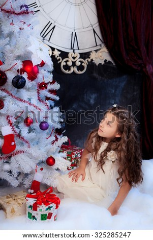 Cute girl sitting with box present under the Christmas tree; adorable child looking at Christmas tree; white fir-tree decorated with red balls and socks - stock photo