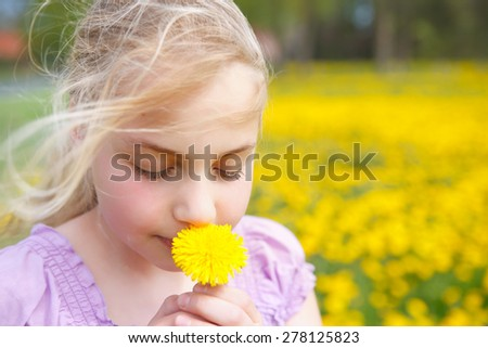 cute girl smells on a flower otudoor in the grass - stock photo