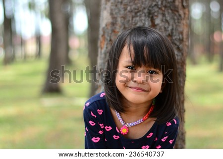 Cute girl smile in front of tree at forest park - stock photo