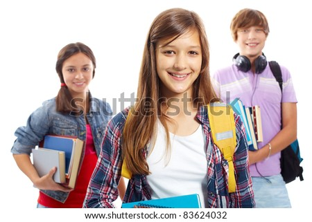 Cute girl smiling at camera with her friends behind - stock photo