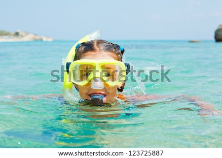 Cute girl snorkelling swimming in the transparent sea - stock photo