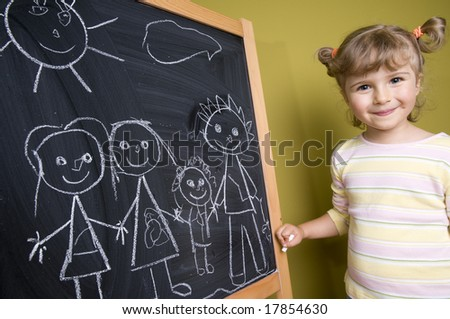Cute girl standing in front of blackboard, drawing family - stock photo