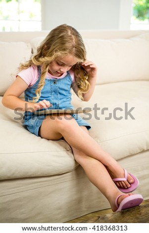 Cute girl using digital tablet while sitting on sofa - stock photo