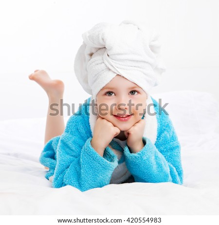 cute girl wearing a bathrobe and a towel after shower in bed at home - stock photo