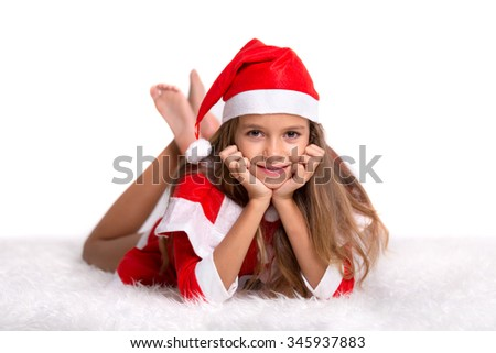 Cute girl wearing a red and white Christmas Santa hat and suit lying on a furry white carpet - stock photo