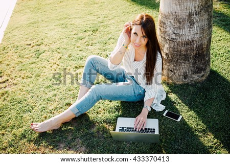 Cute girl with a smart phone and a laptop is looking at camera while sitting in a park. Model look woman in a striped shirt and the jeans is surfing the web while sitting on a grass in a sunny day. - stock photo
