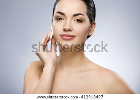 Cute girl with black fixed hair behind, big eyes and naked shoulders, looking at camera and cleaning face with cotton pad at gray studio background, close up. - stock photo