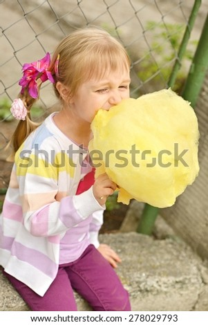 Cute girl with cotton candy - stock photo