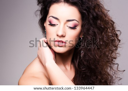 cute girl with curly hair wearing make-up - studio shot - stock photo