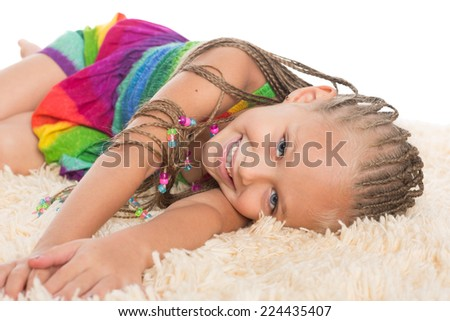 Cute girl with dreadlocks lays on the mat. Girl six years. - stock photo