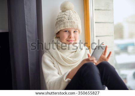 Cute girl with long hair sitting alone near window with mobile phone. - stock photo