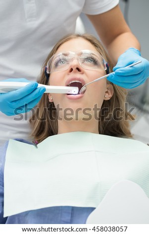 Cute girl with opened mouth in blue shirt, patient bib and protective eyewear. Next to her there is a dentist in a white uniform with blue latex gloves. He diagnoses her teeth with a LED intraoral - stock photo