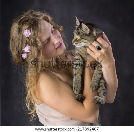 cute girl with roses in her hair and with a cat on his hands - stock photo