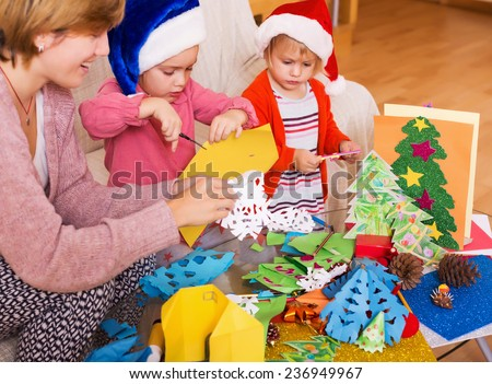 Cute girls in Santa hats and smiling mom doing applique work  at home - stock photo