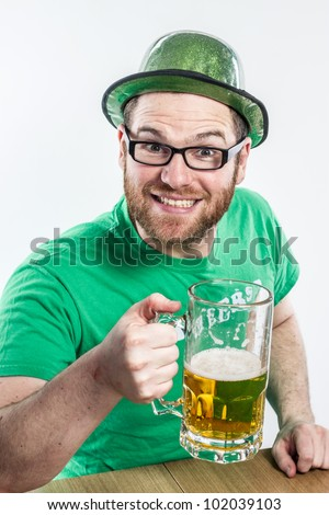 Cute glasses Irish man in green shirt St. Patty's Day pub drinking large glass mug of beer to Ireland - stock photo
