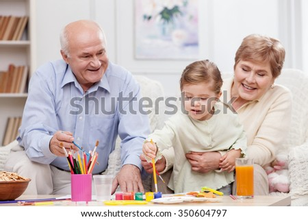 Cute grandparents are teaching their small granddaughter to paint. They are sitting on the couch and laughing. The woman is embracing the kid. The girl is holding a paintbrush with interest - stock photo