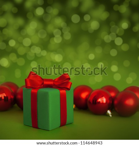 Cute green gift with red christmas balls on green abstract light background - stock photo