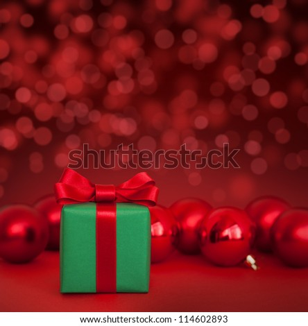 Cute green gift with red christmas balls on red abstract light background - stock photo