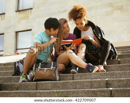 cute group of teenages at the building of university with books huggings, back to school - stock photo