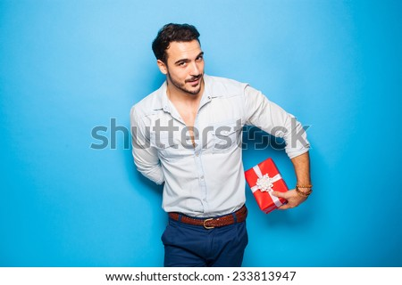 cute guy hiding a christmas gift behind him on blue background - stock photo