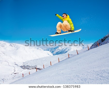 Cute handsome snowboarder man holding snowboard in the air jumping in ski park - stock photo