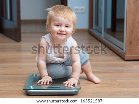 Cute happy baby check own weight on home scales - stock photo
