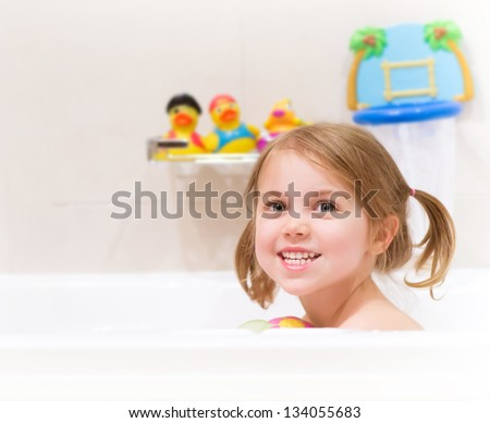Cute happy baby girl taking bath with foam and toys, child's hygiene, healthy lifestyle, carefree childhood concept - stock photo