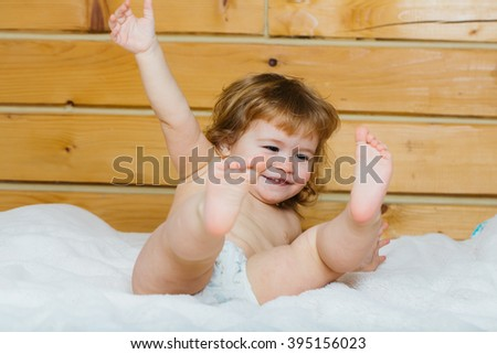 Cute happy beautiful smiling playful child boy with wet hair sitting in hothouse bath white fluffy towel naked indoor on wooden background, horizontal picture - stock photo