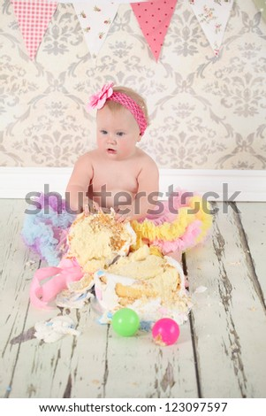 Cute happy blond baby girl in pink and yellow tutu and flower head band sitting on vintage wooden floor and background by smashed double tier polka dot decorated pink blue and white fondant iced cake - stock photo
