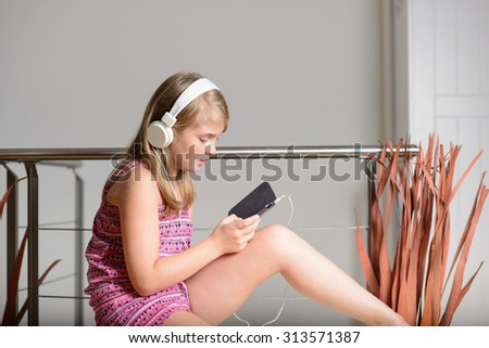 Cute happy blonde girl listening to music on headphones - stock photo