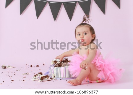 Cute happy brunette baby girl in pink tutu sitting on background by her double tier pink and purple fondant iced birthday party cake reaching out touching and destroying it looking at camera surprised - stock photo
