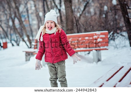 cute happy child girl in red coat throwing snow and laughing on the walk in winter snowy park - stock photo