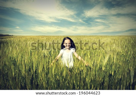 Cute happy child runs across the field of wheat - stock photo