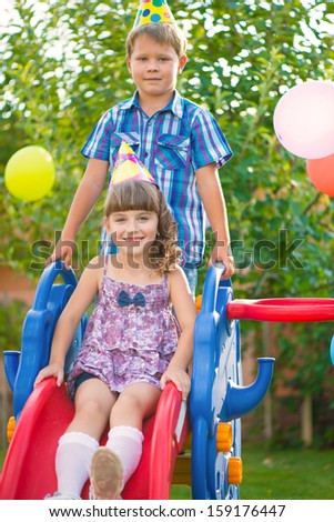 Cute happy children sliding at playground - stock photo