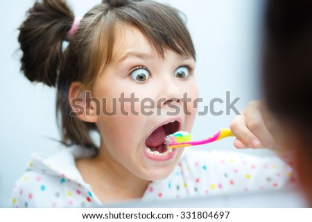 Cute happy girl brushes her teeth in the bathroom - stock photo