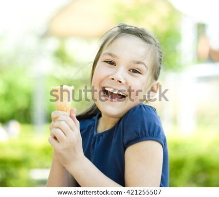 Cute happy girl is eating ice-cream - stock photo